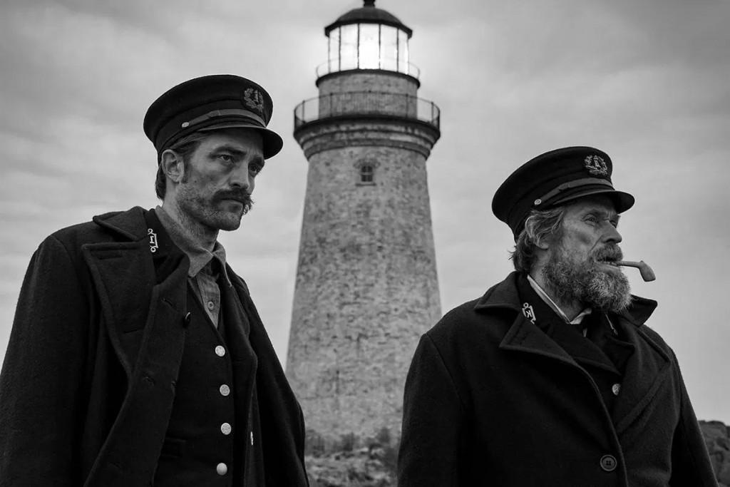Ephraim Winslow (Robert Pattinson), the lighthouse (phallic symbol), and Thomas Wake (Willem Dafoe) stare out into the sea.